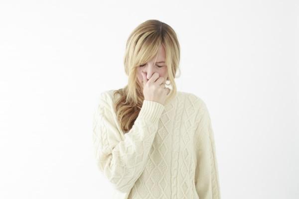 臭くて鼻を抑える女性